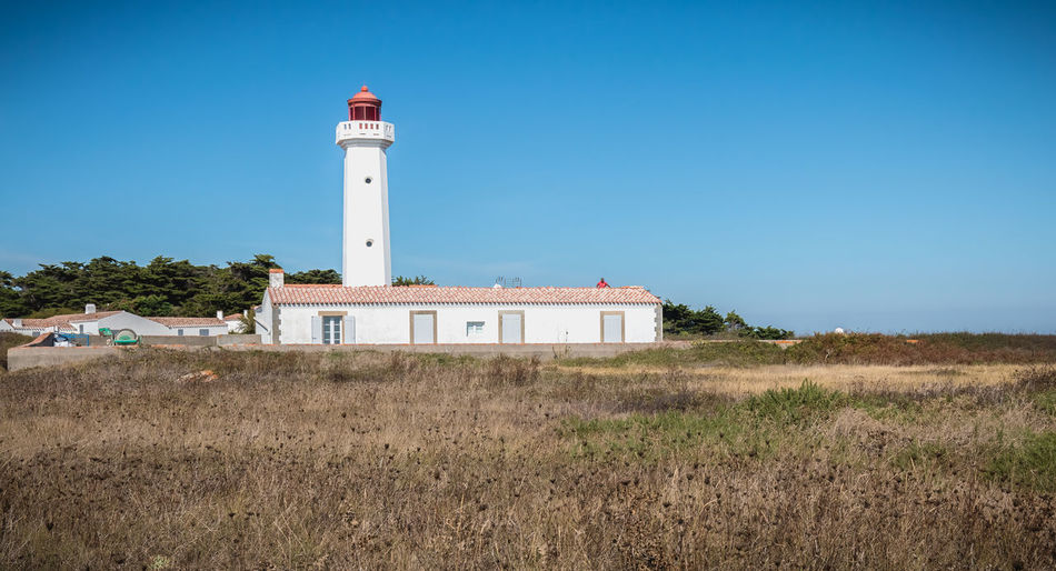 Lighthouse on field by building against clear blue sky