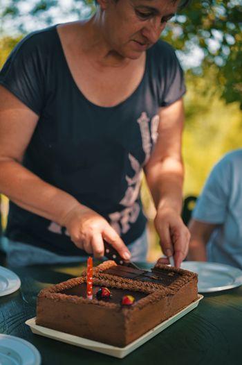 Senior woman cutting birthday cake