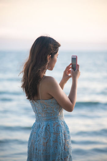Young woman photographing while standing on sea against sky