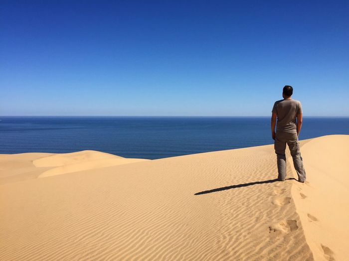 Rear View Of Man Standing On Sand Dune Against Clear Sky