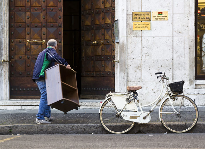 Side view of man with bicycle standing against brick wall