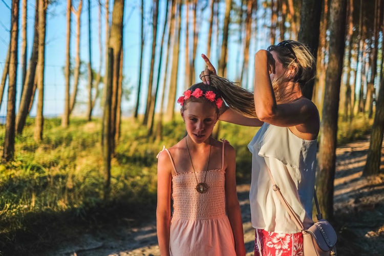 Woman Adjusting Hair Of Daughter At Forest