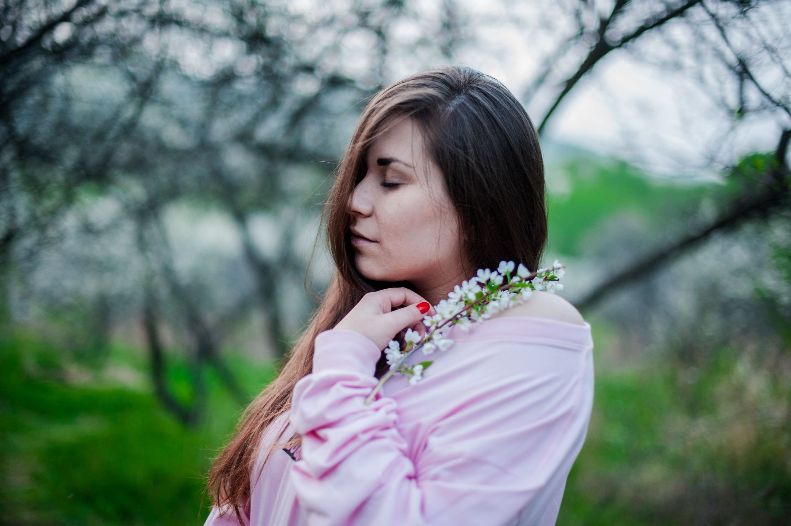 plant, women, one person, headshot, focus on foreground, tree, real people, portrait, hairstyle, lifestyles, long hair, leisure activity, nature, day, brown hair, pink color, flower, hair, outdoors, contemplation, beautiful woman