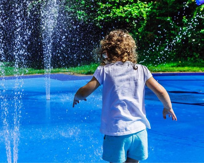 Summer is here Water Swimming Pool Motion Wet Splashing Rear View Spraying Blue Fun One Person Leisure Activity Outdoors Enjoyment Day Standing Real People Lifestyles Water Park Happiness Young Adult