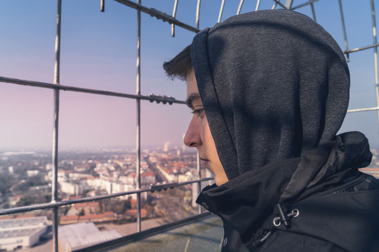 Portrait of young man looking at cityscape against sky
