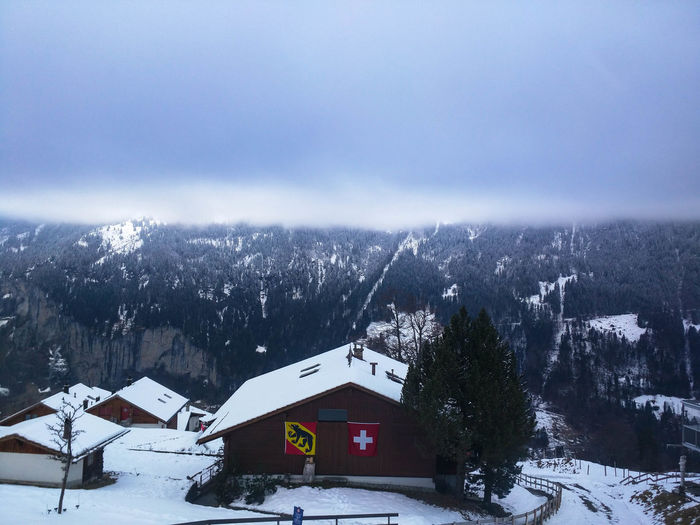 Snow covered houses by mountains against sky