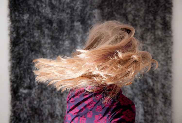 Side view of woman tossing blonde hair