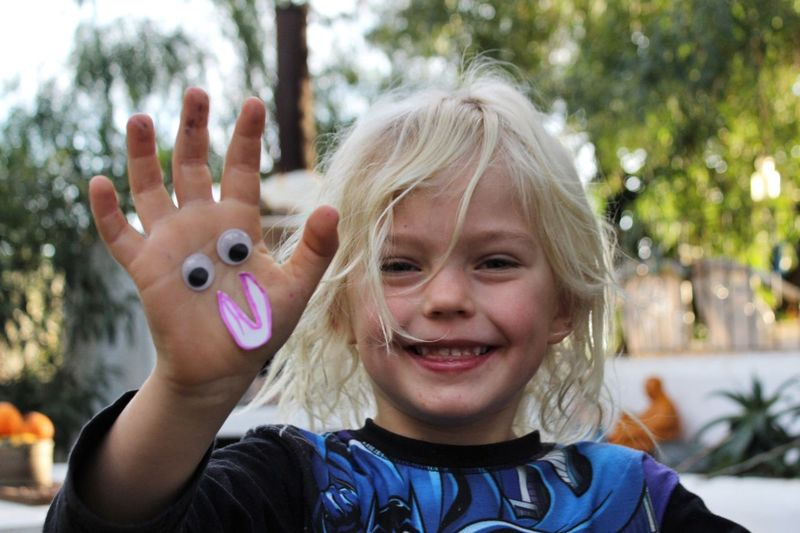 Portrait of smiling girl showing hand with googly eyes