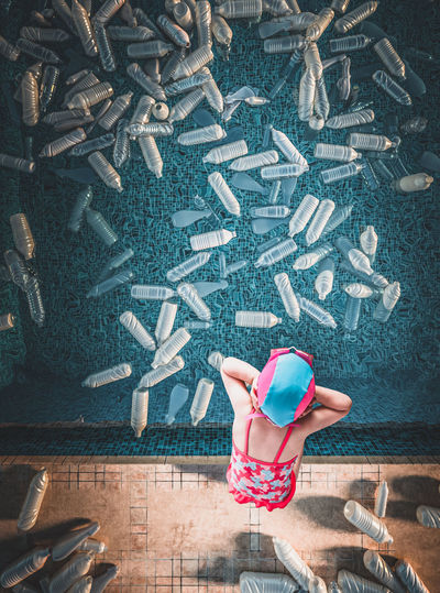 Directly above shot of girl standing by plastic bottles in swimming pool