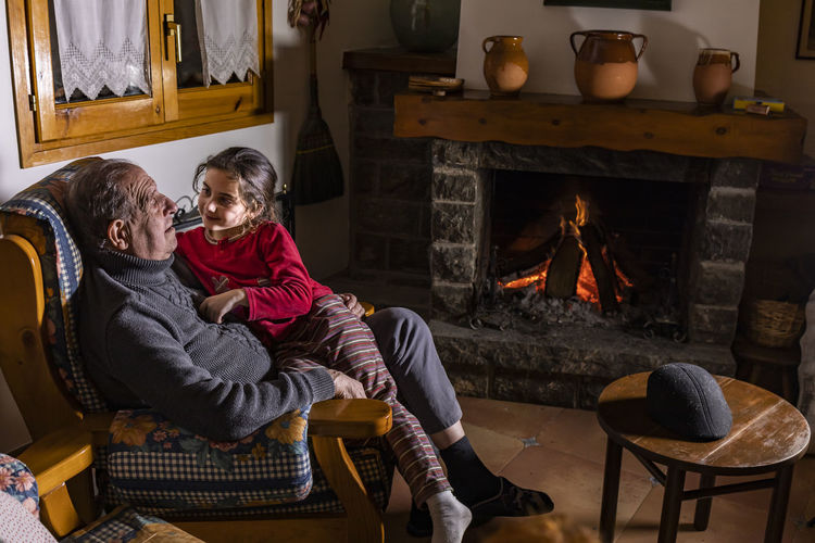 Grandpa and granddaughter Grandparent Grandfather Grandchild Granddaughter Sitting Men Two People Indoors  Togetherness Real People Fire Adult Males  Burning Fire - Natural Phenomenon Lifestyles Bonding Love Emotion Fireplace Women Heat - Temperature Winter Domestic Room Positive Emotion Mature Men Warm Clothing Couple - Relationship