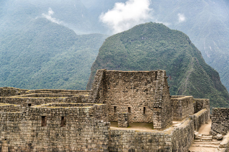 Old ruins against rocky mountains during foggy weather at machu picchu