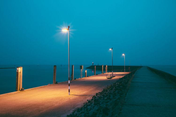 Illuminated street light on beach against clear blue sky at night