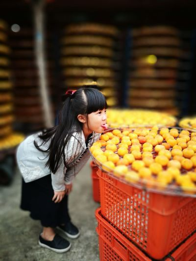 Girl Sticking Out Tongue By Sweet Food In Container On Crates