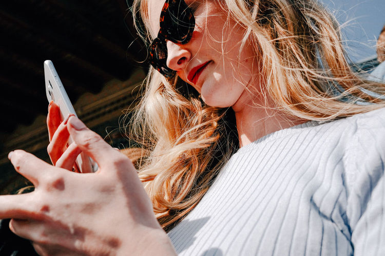 Low angle view of woman in sunglasses using smart phone on sunny day