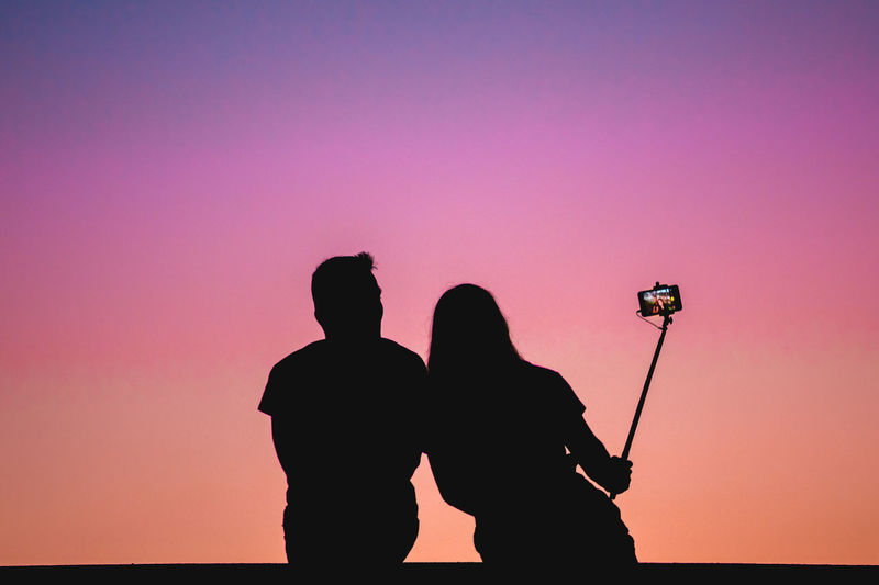 Silhouette Woman With Man Taking Selfie Against Sky During Sunset