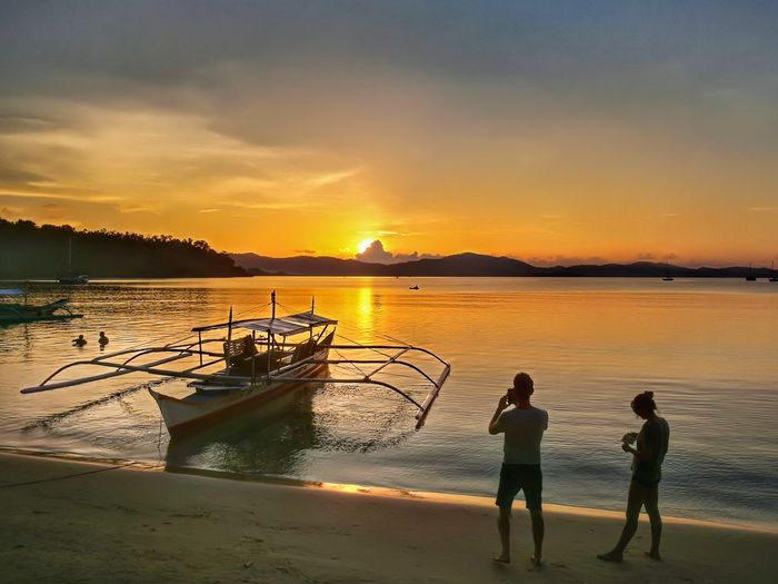 Tourist couple photograph beach sunset, Port Barton Palawan Philippines Silhouette Adventure Holiday Banca Boat Beach Dream Holiday Outrigger Photograph Sunset Scenics - Nature Sunset Sunset Over Water Tourist Couple Tropical Island Two People