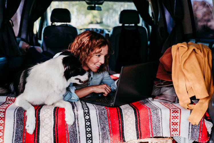 Woman using laptop while lying with dog in camper trailer