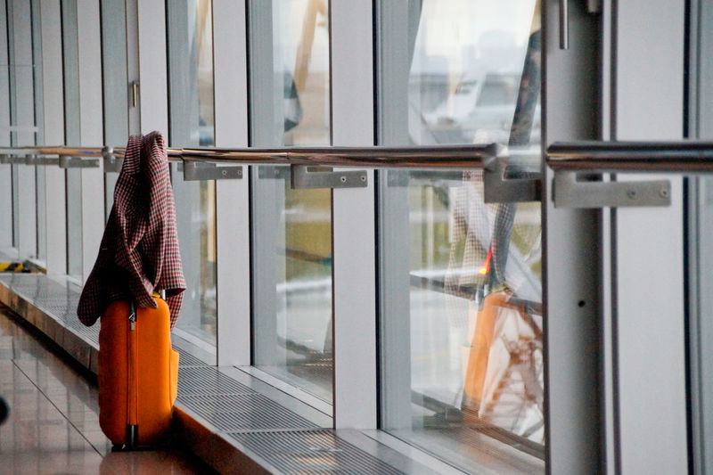 Jacket on suitcase by window at airport