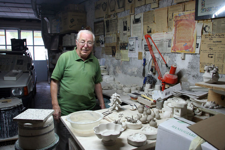 Workshop of the ceramist Arts And Crafts Workshop Workshop View Adult Adults Only Ceramist Ceramista Eyeglasses  Indoors  Industry Large Group Of Objects Looking At Camera Occupation One Man Only One Person One Senior Man Only Only Men People Portrait Real People Senior Adult Standing Working Working Seniors Workshop