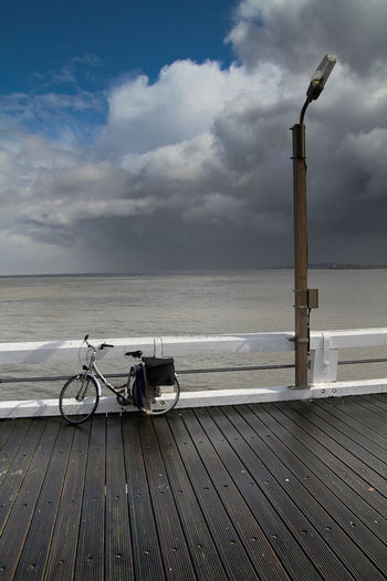 Bicycle on pier against cloudy sky