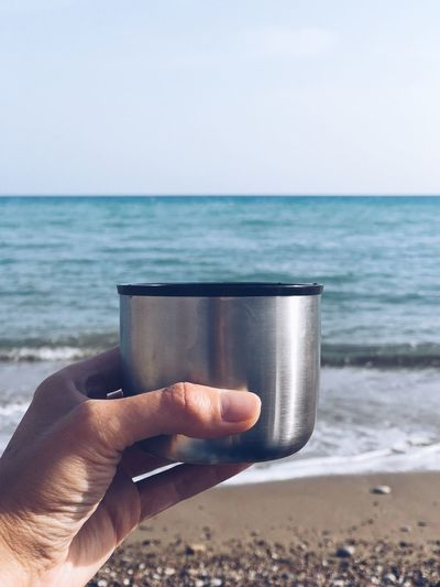 Sea and tea Paramali Cyprus Tea Thermos Sea Beach Human Hand Horizon Over Water Human Body Part Sand Water Human Finger Holding Drink Outdoors