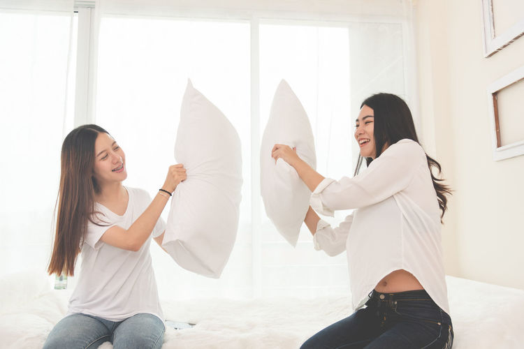Happy friends pillow fighting on bed at home