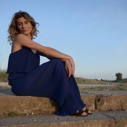Portrait of woman sitting against blue sky