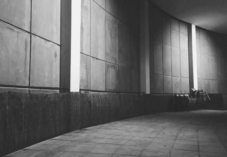 Empty Walkway Against Illuminated Wall