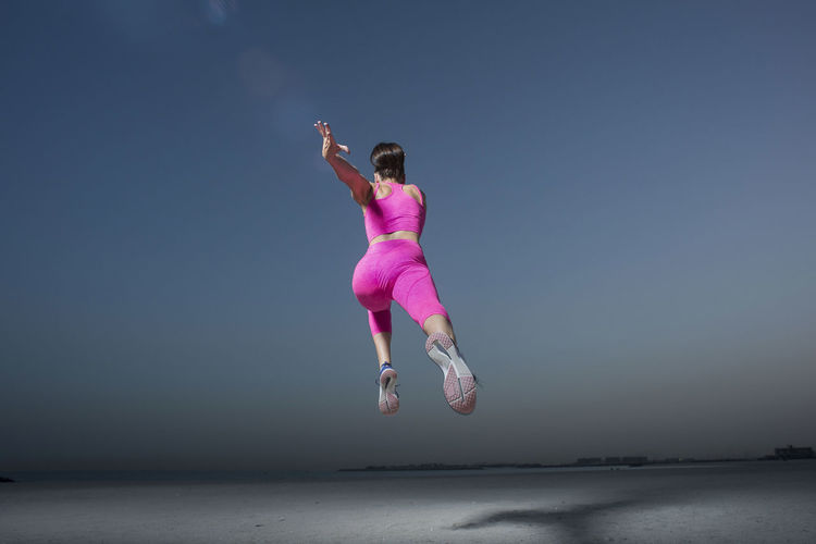 Full Length Of Woman Jumping Against Sky