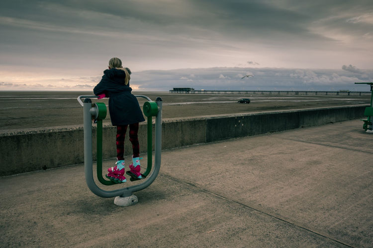 Rear View Of Girl Standing On Exercise Equipment At Promenade