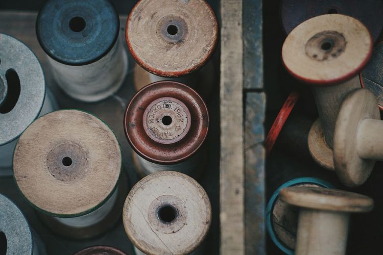 High Angle View Of Thread Spools In Wooden Container