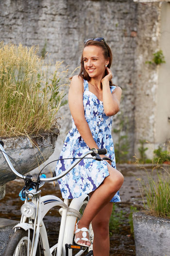 Happy young woman with bicycle standing against wall