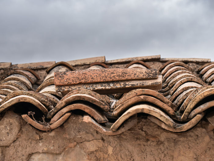 Low angle view of old roof tiles against sky