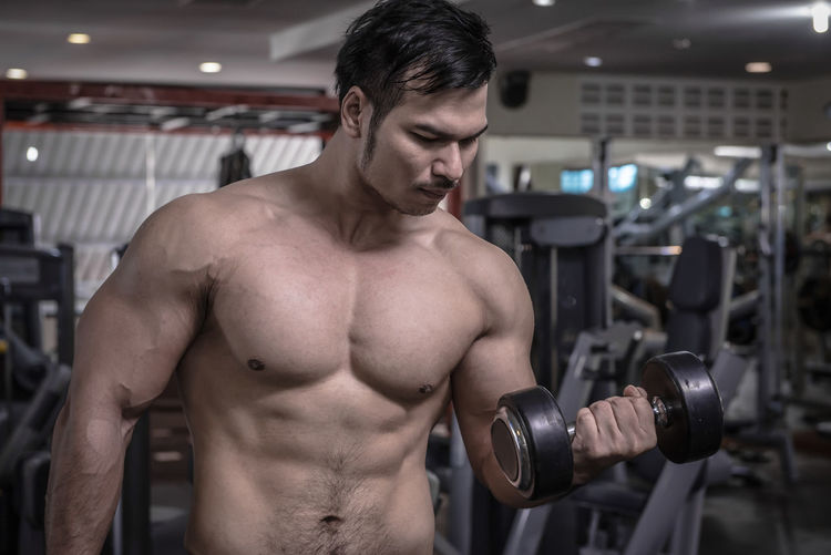 personal fitness trainer show his muscles or Strong bald bodybuilder with six pack Adult Athlete Bicep Body Conscious Chest Exercise Equipment Exercising Gym Healthy Lifestyle Indoors  Lifestyles Men Muscular Build One Person Shirtless Sport Sports Training Strength Vitality Weight Weight Training  Weights Wellbeing Young Adult Young Men