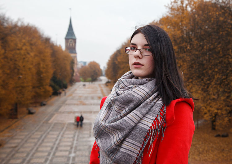 Portrait of young woman standing against trees during winter