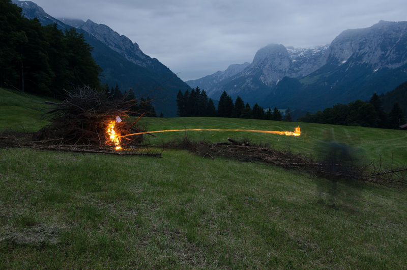 Blurred Motion Of Person Burning Firewood On Field Against Mountains In Winter