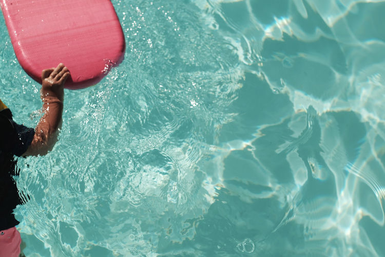 Midsection of child holding pool raft in swimming pool