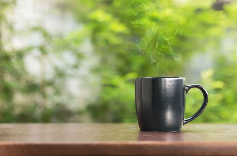cup of coffee Close-up Coffee Coffee Cup Cup Day Drink Focus On Foreground Food And Drink Green Color Hot Drink Mug Nature No People Outdoors Plant Refreshment Selective Focus Smoke - Physical Structure Steam Still Life Table Tea Cup Wood - Material