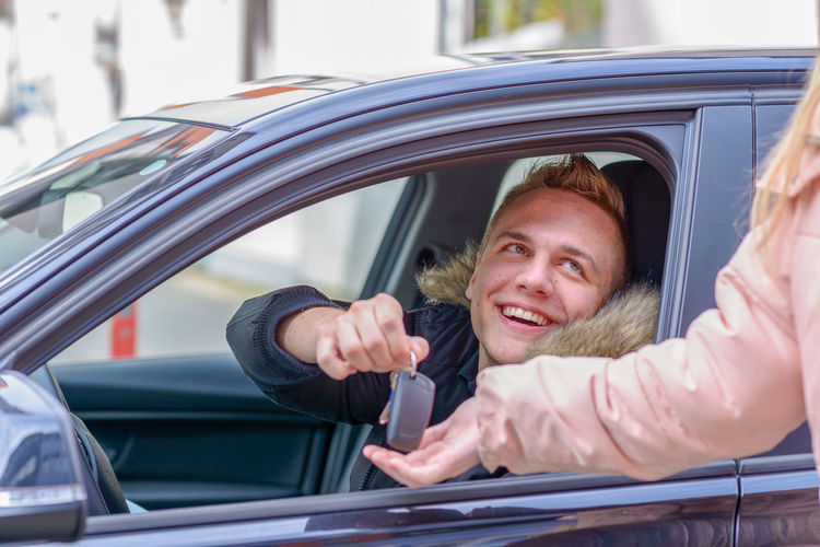 Cropped image of woman giving car key to man
