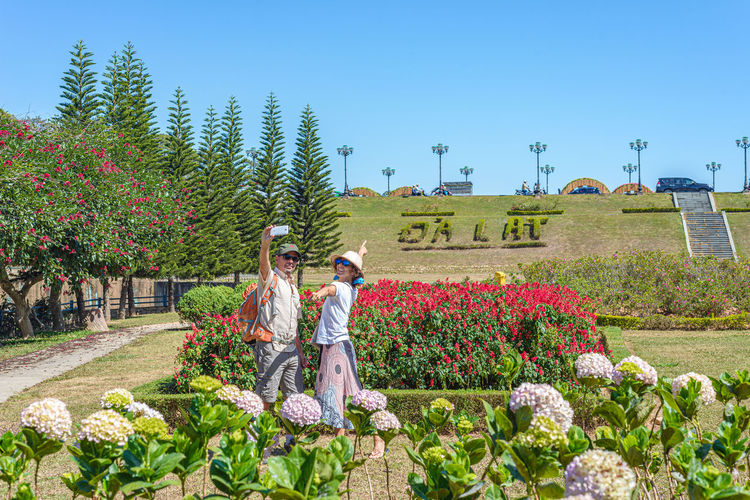 People on flowering plants against sky