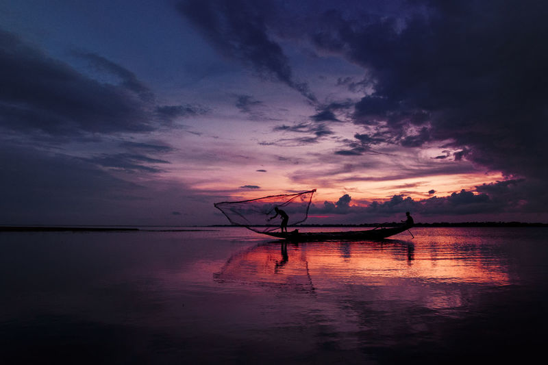 Silhouette fishing boat in sea against sky during sunset