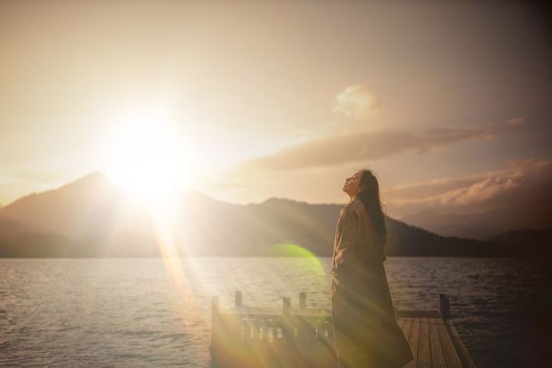 Woman standing by sea against sky during sunset