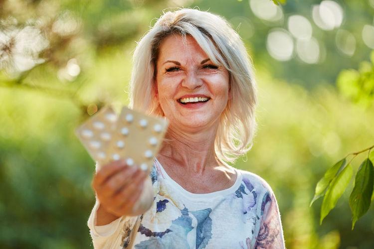 Portrait of smiling senior woman holding blister packs