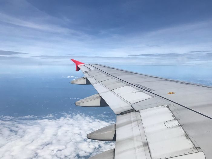 Airplane flying over clouds against sky