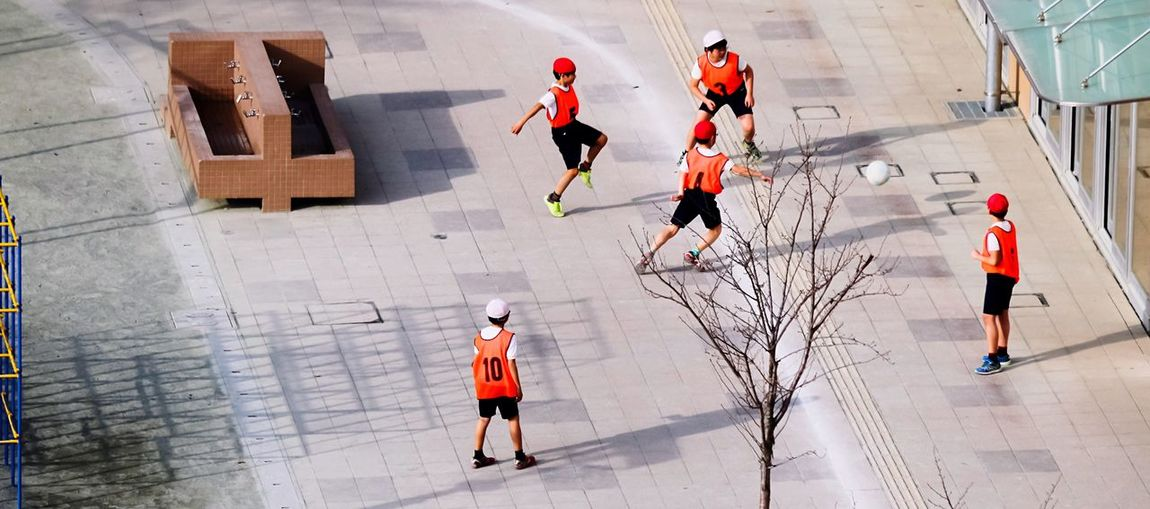 High angle view of children playing soccer on playground
