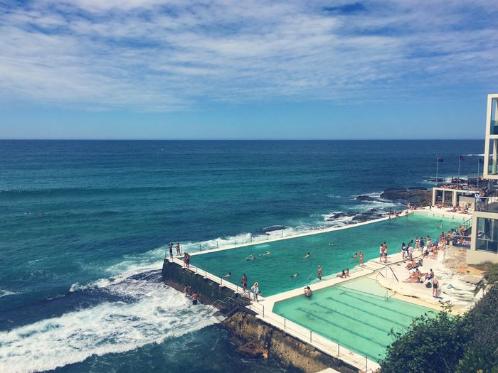 High angle view of people at infinity pool with sea in background against sky