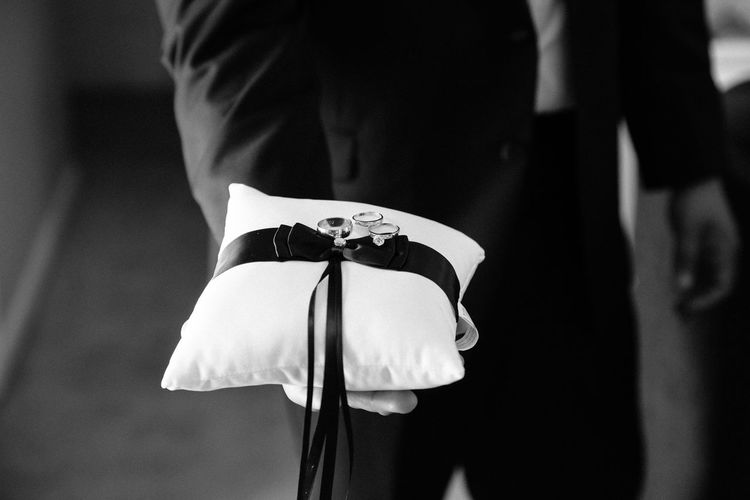 Midsection Of Bridegroom Holding Wedding Rings On Cushion