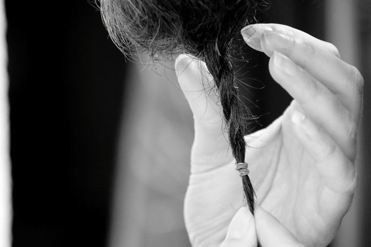 Cropped hands of woman holding braided hair