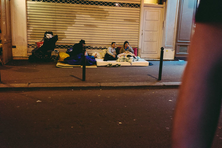 Family Paris Poverty Lives. Beggar Building Exterior Childhood Day Destitution French Indigence Medium Group Of People Neediness Outdoors Penury People Playing Poorness Poorness Behind The Luxuries Poverty Real People Sitting Street Togetherness
