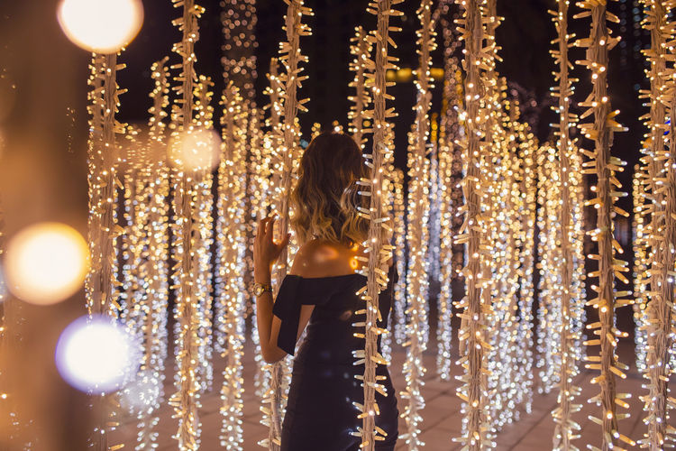 Rear view of woman standing against illuminated lights